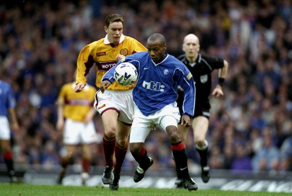 18 Mar 2000: Rod Wallace of Glasgow Rangers shields the ball from Derek Adams of Motherwell during the Scottish Premier Division match at Ibrox Stadium in Glasgow, Scotland. Glasgow Rangers won the match 6-2. Mandatory Credit: