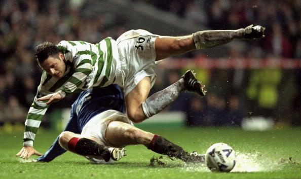 Mark Viduka of Glasgow Celtic is tackled by Craig Moore of Glasgow Rangers